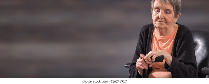 Old woman sitting and holding her cane