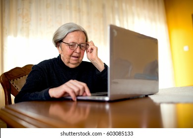 Old woman sitting at home looking at laptop surfing internet.
