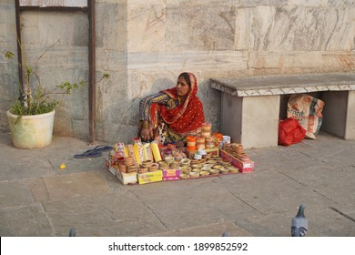 An old woman sitting on Indian street market and selling colorful bangles. Lady selling bangles on the streets of Udaipur city. : Udaipur India - June 2020. VGT