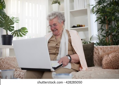 Old woman sitting on sofa and holding a laptop