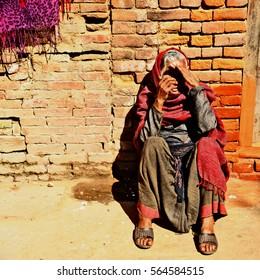 Old woman sitting on street. She got a sunbath in every morning to warm her body. At Bhaktapur Kathmandu Nepal 19.02.2013