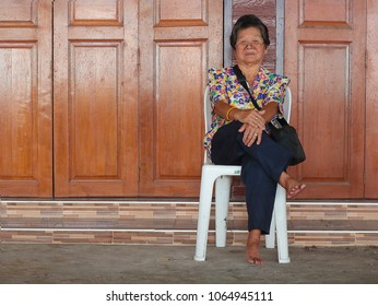 Old woman sitting on white chair and her legs crossed | vintage wooden doors background
