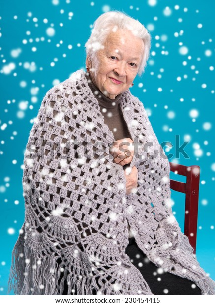 Old woman sitting in shawl on a chair. Christmas and holidays concept