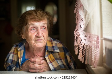 Old woman sitting at a table in his house, with a worried expression on his face.