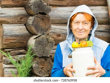 old woman smile and hold can full of ripe apples, she stand against weathered wooden house wall (log hut)
