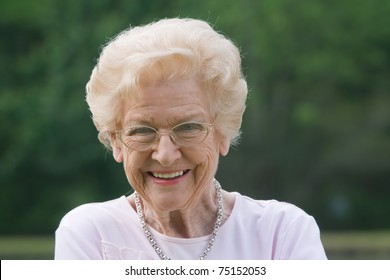 Old woman smiling outside during the day