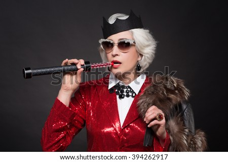 c4856b28ae2 Old woman smoking electronic hookah lounge while wearing crown and  sunglasses over black background. Rich