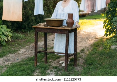 an old woman stands and waits, in white vintage clothes, in the courtyard, near the table. on the table is an old clay jug and an old copper basin with water and cloth. next are the clothespins