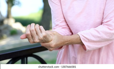 Old woman stretching numb arm, weakness of muscles in senior age, arthritis