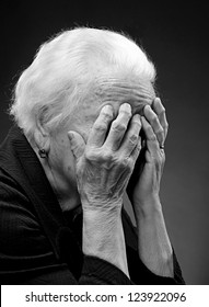 Old woman suffering from headache on a gray background