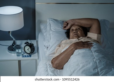 Old woman suffering from insomnia is trying to sleep in bed at night