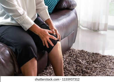 old woman suffering from knee pain at home, health problem concept