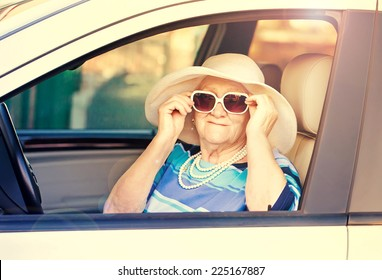 old woman in sunglasses sitting in the car .