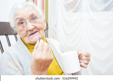 Old woman taking her daily medication with water.