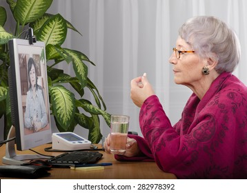 Old woman taking a pill during medical consultation on-line. Grey haired woman in crimson cape sitting opposite monitor. On the screen doctor is consulting her. Side shot