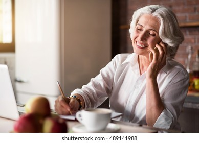 Old woman talking on the phone while taking notes