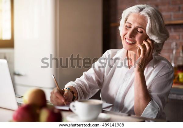 Vieille femme parlant au téléphone en prenant des notes
