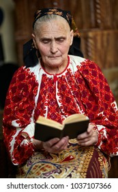 Old woman in traditional costume reading a book indoor