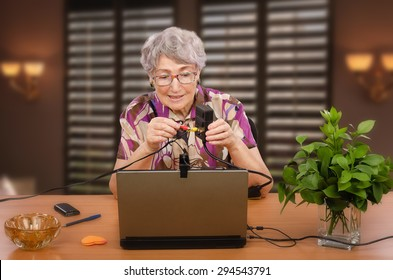 Old woman is trying to install audio video adapter by herself looking video manual in internet