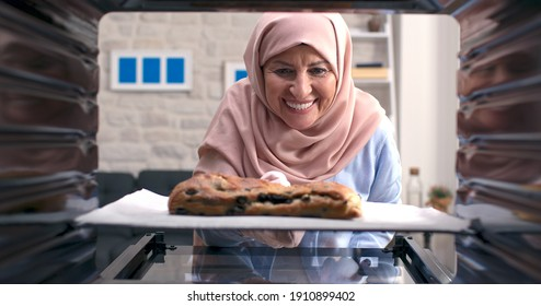 The old woman in a turban takes out delicious, rich grain and olive bread from the oven. Shooting through the oven.