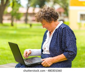 Old woman typing with her broken arm on her laptop to order and shop from the internet.