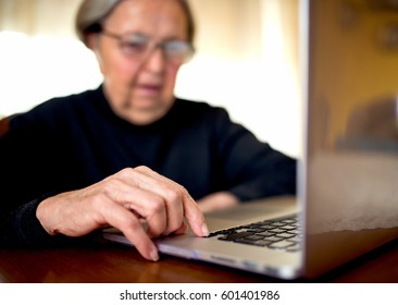 Old woman typing on laptop.