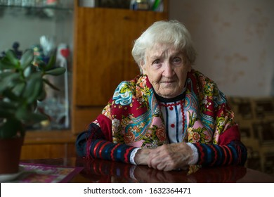 An old woman in ukrainian clothes sitting in home.