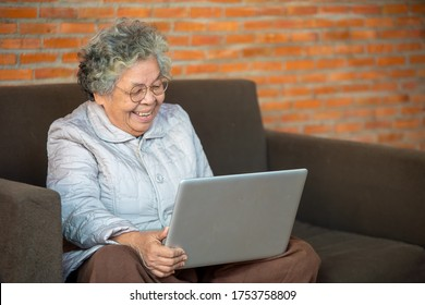 Old woman using her laptop and web surfing,Working from home in quarantine lockdown,Social distancing concept.