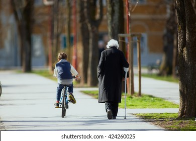 Old woman walking down the street with walking stick and in front of her a young child is riding a bike