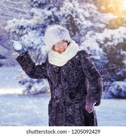 Old woman walking at winter park. Senior outdoors