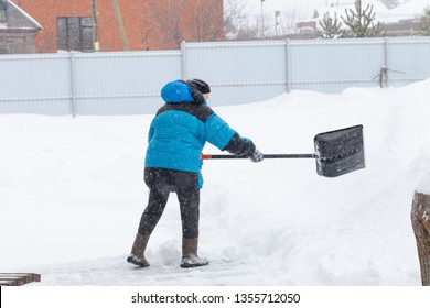 Old woman in warm blue jacket clears a snowdrifts with a snow shovel.