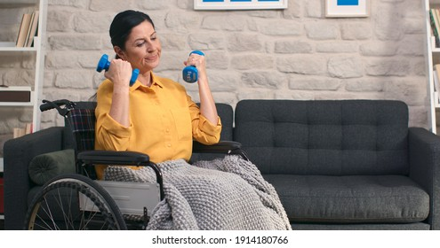 Old woman in wheelchair exercising and lifting weights in a living room. Rehabilitation of young woman in wheelchair. Home exercise, fitness, rest and lifting.