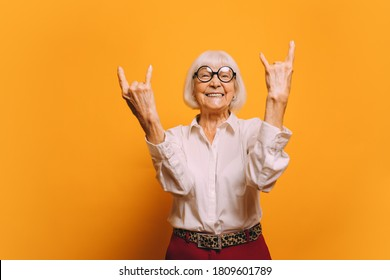 Old woman with white hair with round glasses wearing white blouse, red pants and leopard print belt standing isolated over orange background. Sign of the horns - Shutterstock ID 1809601789