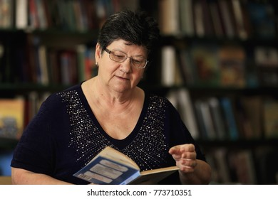 an old woman wore the glasses and reads a book in the library