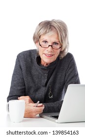Old woman working with her laptop with a cup of coffee on her side