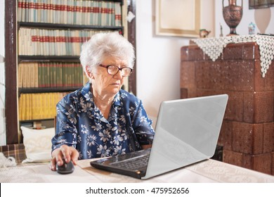 Old woman working on laptop computer at home.