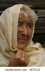 old woman wrapped in a beige scarf