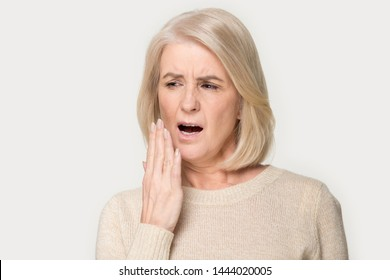 Old woman yawn cover mouth with hand being bored. Elderly female feeling exhausted, sleepy, tired, overworked, no energy headshot. Lady in years gaping portrait at studio isolated on grey background