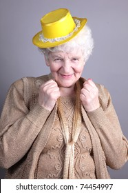 Old woman at yellow hat isolated against grey background