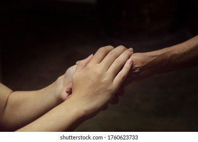 An old woman and a young holding hands together