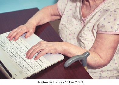 Old woman's hands and laptop.