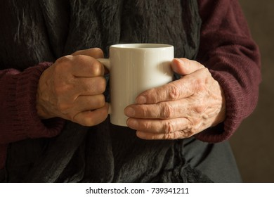 Old woman's wrinkled hands holding a mug with a drink - closeup