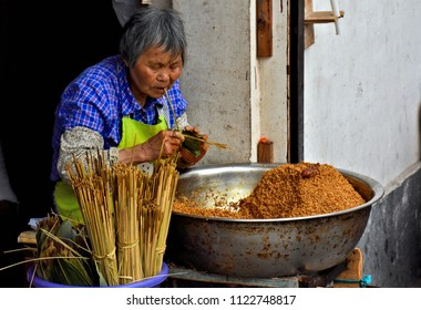 Old woman-street vendor-making Zongzi (traditional Chinese food). Buying street food is popular and entertaining activity among tourists and locals in China. Photo taken 2018-05-28  in Zhujiajiao.