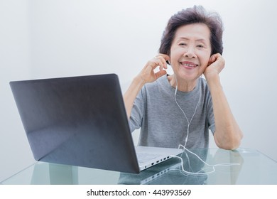 old women  listening to music from labtop