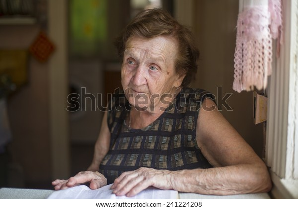 Old women sitting and reading the book in the kitchen.