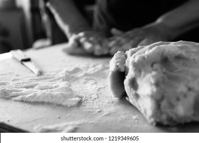 Old women's hands kneading gnocchi, a type of pasta made of potato, on a wood table in background with dough and flour in foreground while a soft side light comes from the window in black and white