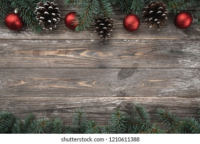 Old wood background with fir branches adorned with baubles and cones. Space for text. Christmas card. Top view. Xmas.