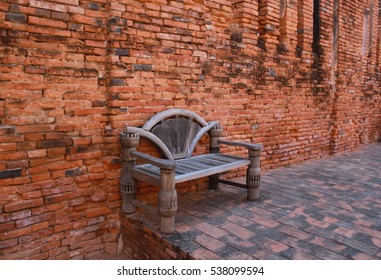 Old wood bench and red brick wall.