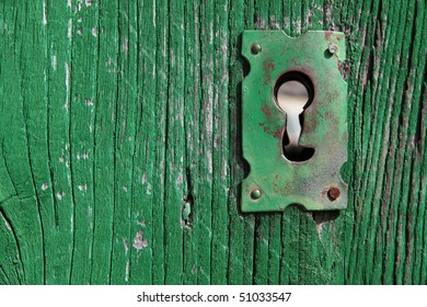 an old wood door with metal lock and keyhole
