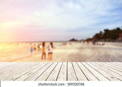 old wood floor on beach with blur people on beach background.